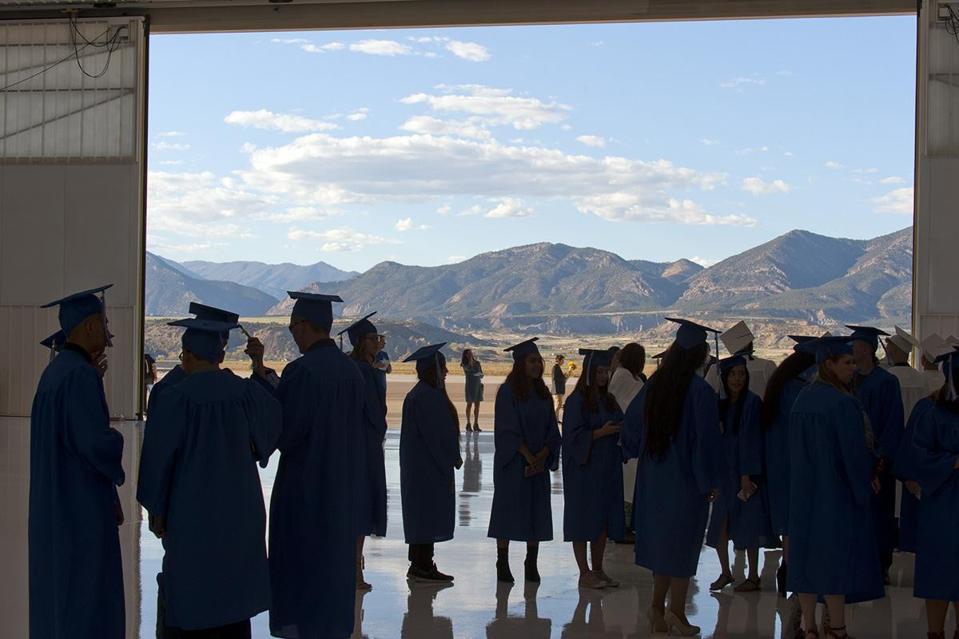 College graduates in shadow of mountain range.