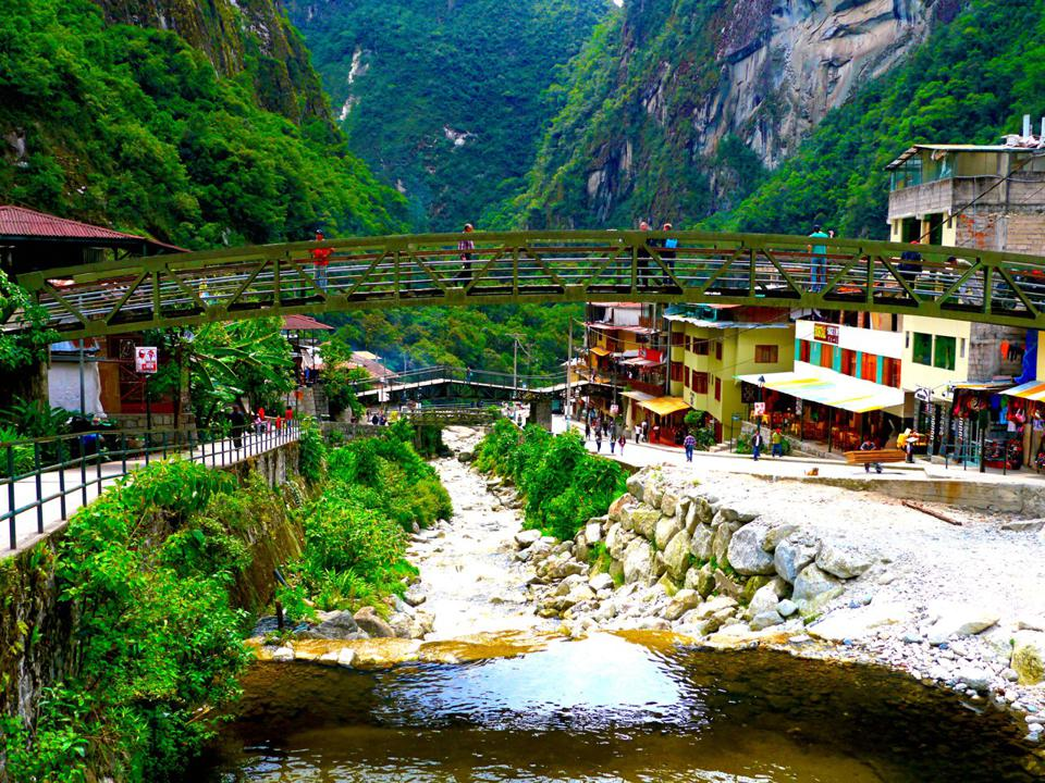 A pedestrian bridge over the river in Aguas Calientes; there are a few buildings on either side and steep green mountains in the background.