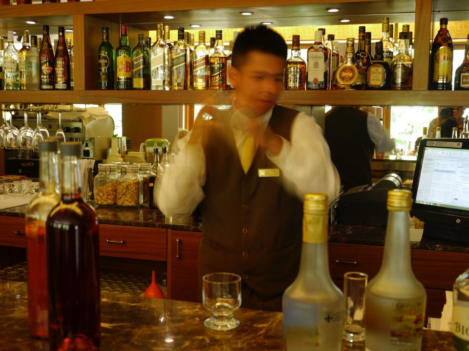 A bartender behind a bar shakes a cocktail shaker just before pouring a pisco sour.