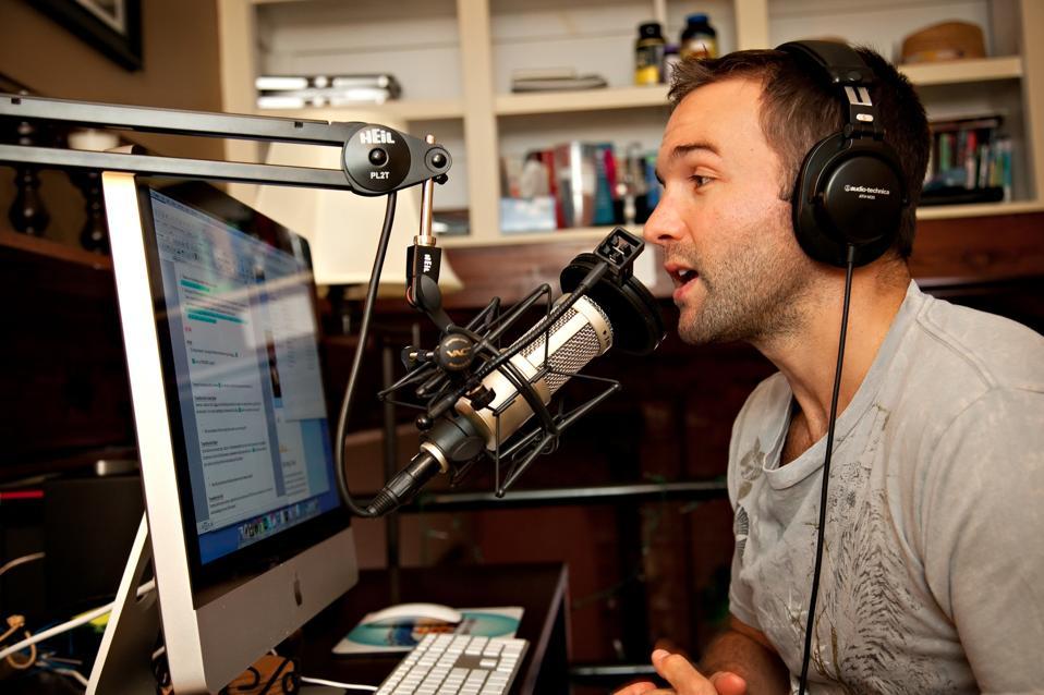 homme entrepreneur assis au bureau menant un podcast