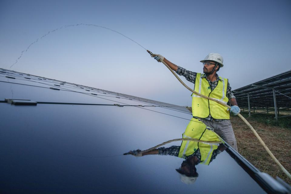 A worker is cleaning solar panels at the Fortum solar park...