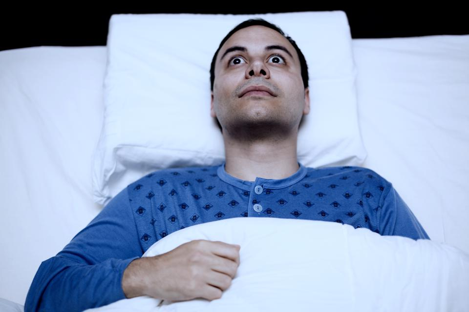 Portrait of an insomniac man trying to sleep.