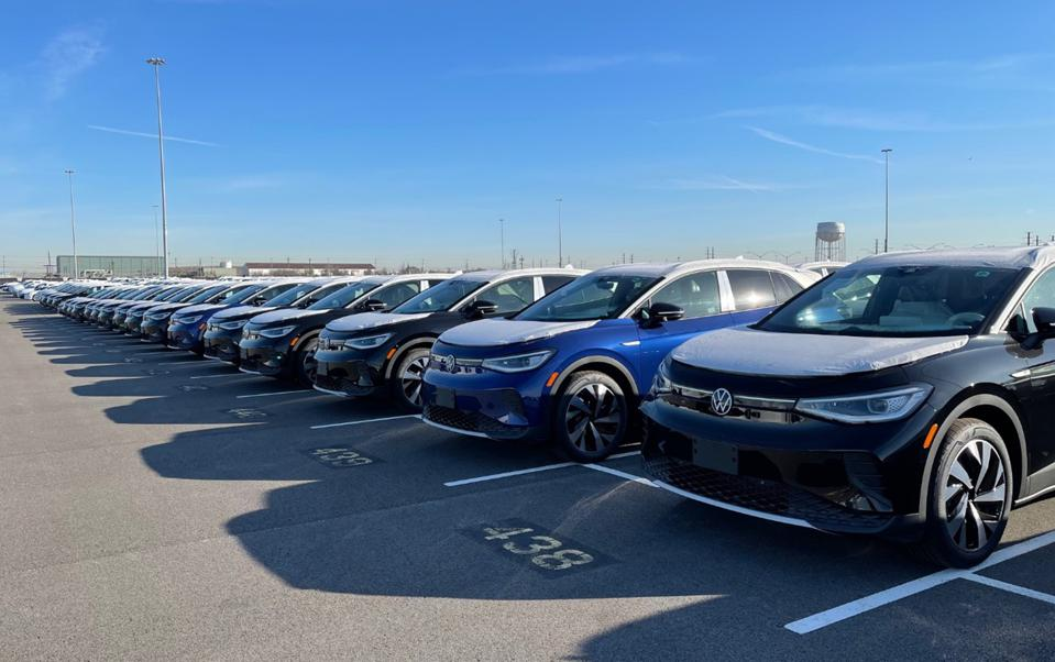 Dozens of VW ID.4 EVs lined up in parking lot.