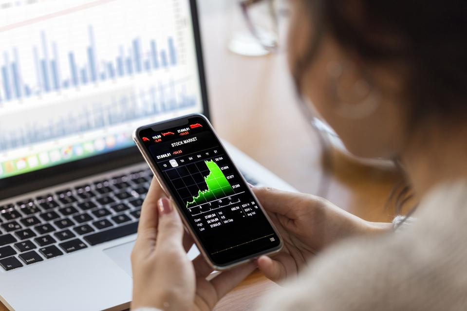 Young finance expert  analyzing financial charts on smart phone