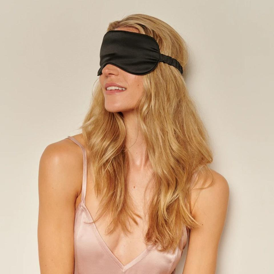 Woman wearing black silk eye sleep mask over face