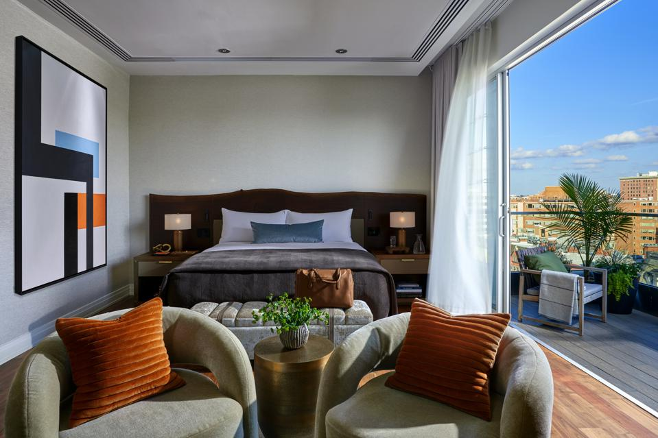A hotel room with a terrace decorated with earth tones and knubby fabrics on contemporary furniture