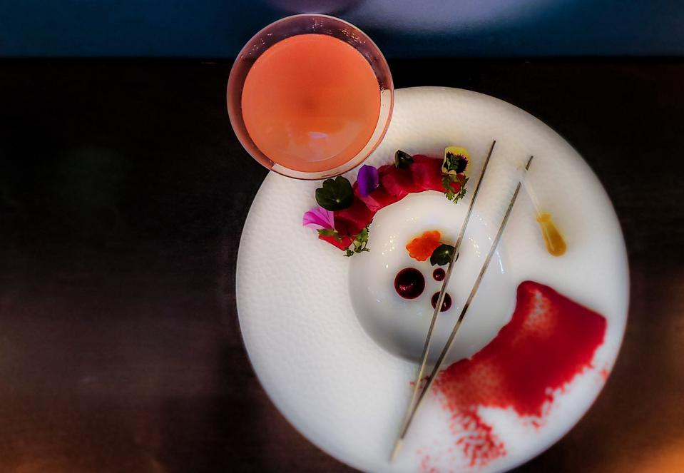 A white plate with slices of raw tuna and an apricot colored cocktail.