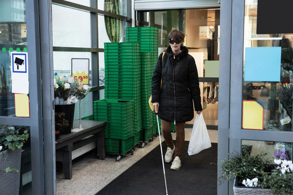 Blind woman shopping while walking with stick in supermarket