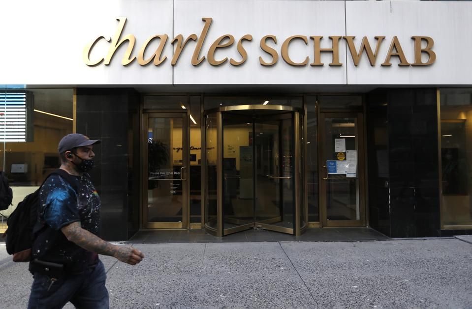 A man wearing a face mask walks past a Charles Schwab sales...