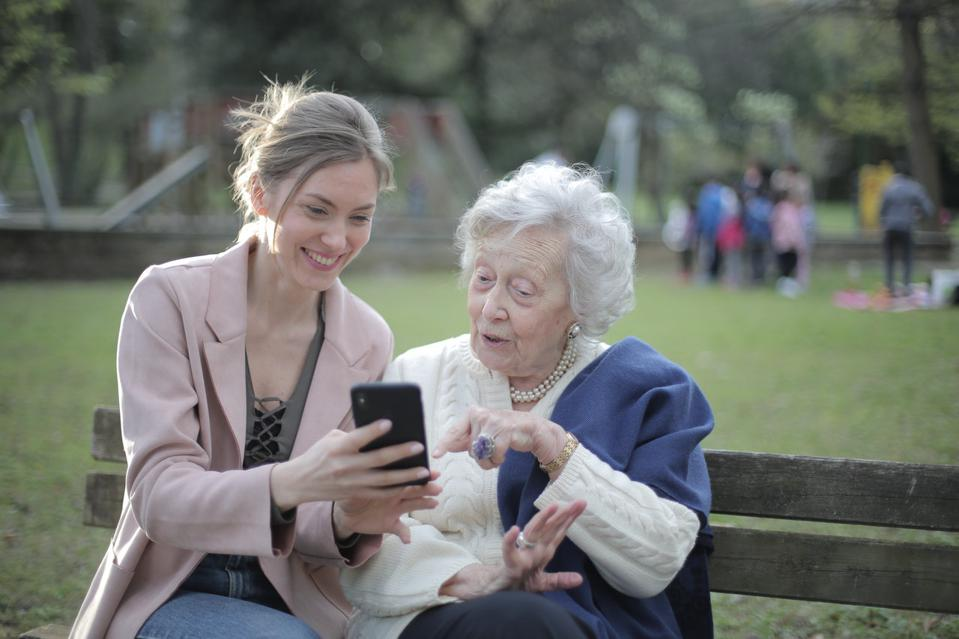 An elderly woman points to a smartphone, which a young women shows to her.