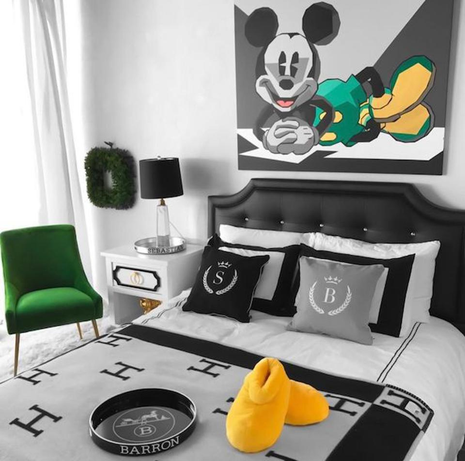 A bedroom with a Mickey Mouse painting by artist Elizabeth Sutton and Hermes bedding.