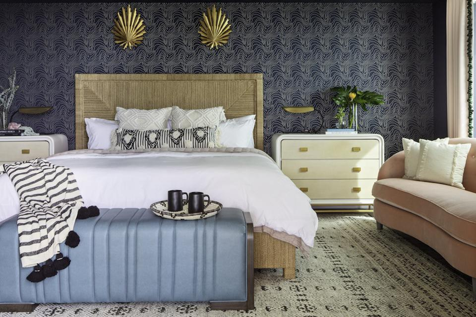 A bedroom with blue wallpaper and a rug