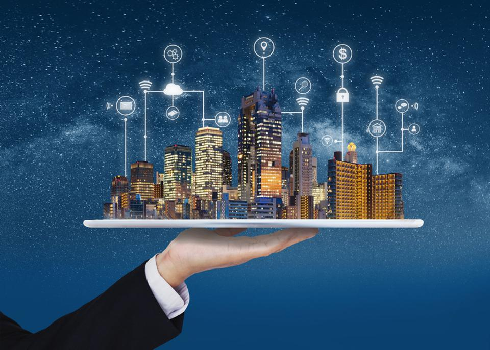 Smart city, building technology, and real estate business. Businessman holding digital tablet with buildings hologram and application programming interface technology