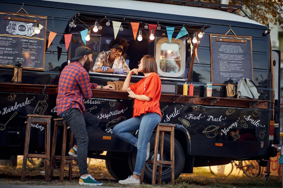 Hipster couple ordering from food truck; Urban lifestyle concept
