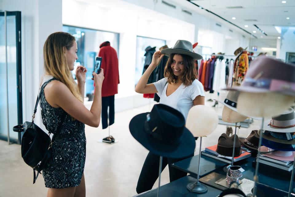 Friends smile at each other while trying on outfits