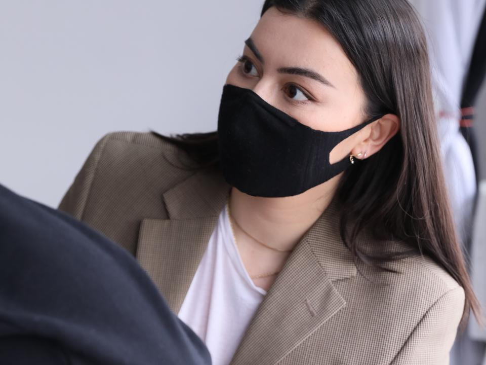 Woman wearing face mask measuring someone for photo shoot