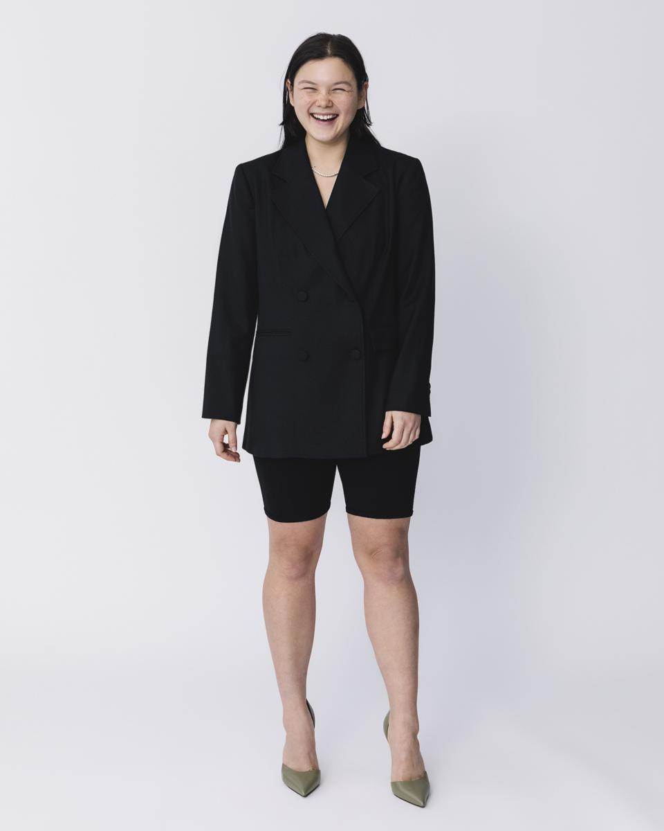 Woman wearing shorts and blazer smiling