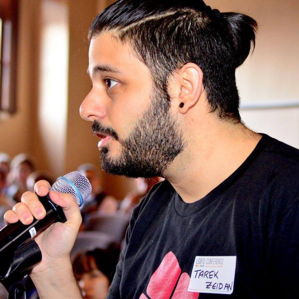 Young Lebanese man with a small pony-tail and a beard, speaking with microphone