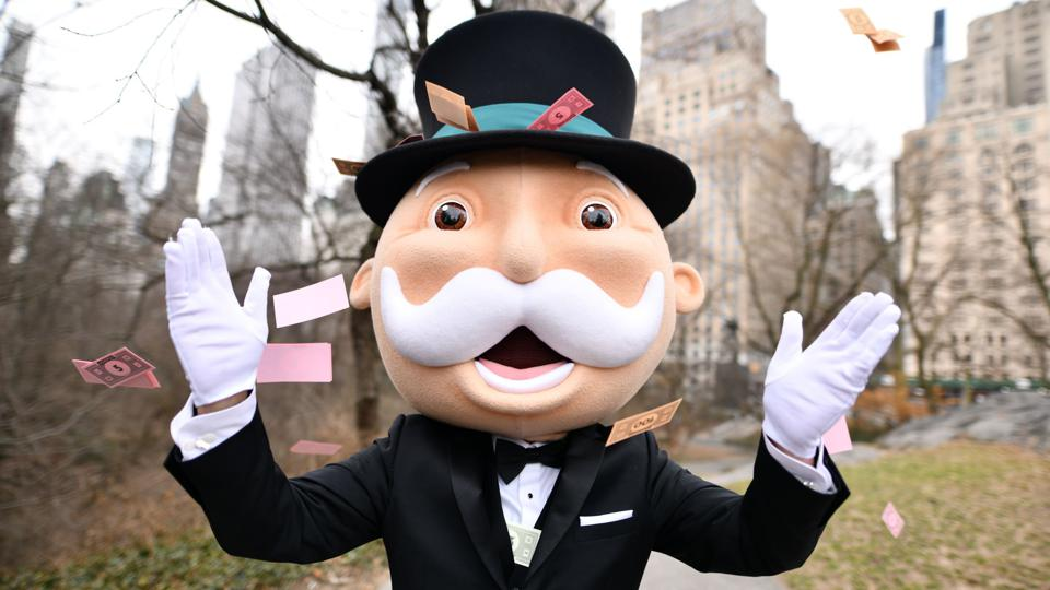 An actor dressed as the Mr. Monopoly mascot surrounded by a flurry of game cards, in New York's Central Park
