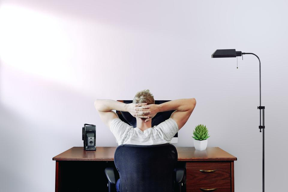 Man seated at desk with hands folded behind his head not working.