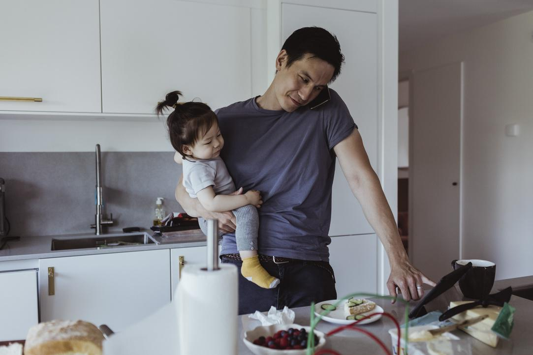 Father talking on smart phone while using digital tablet while carrying baby son in kitchen