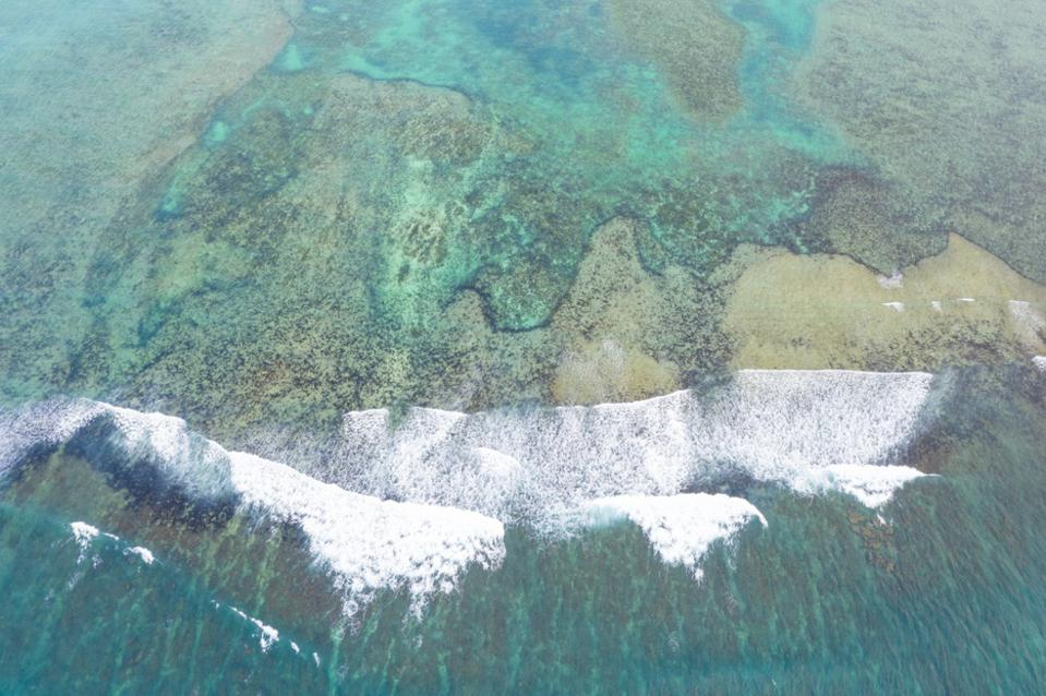 Shot from above, waves break on a coral reef beyond which is calm water