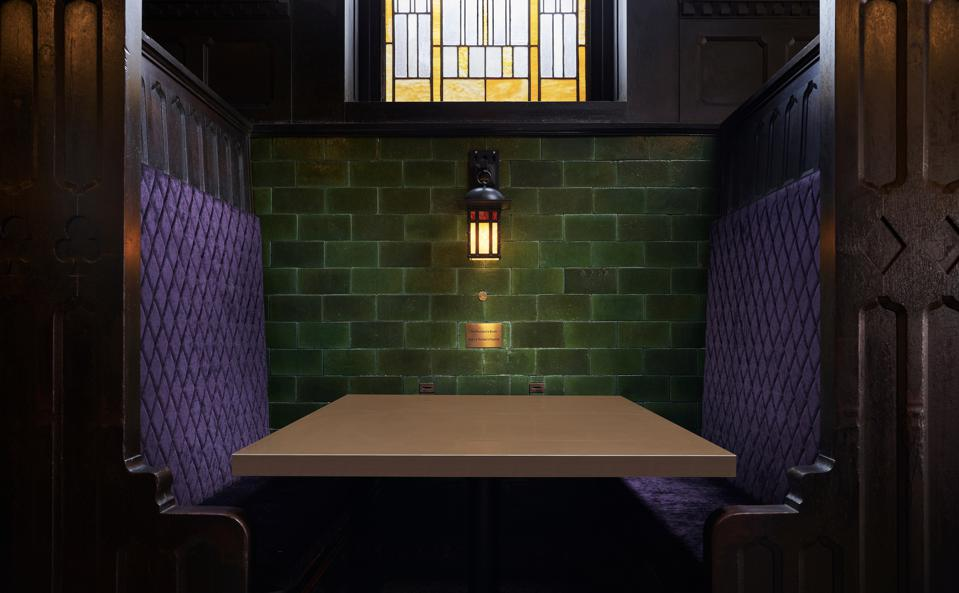 purple restaurant stand with green wall and stained glass window