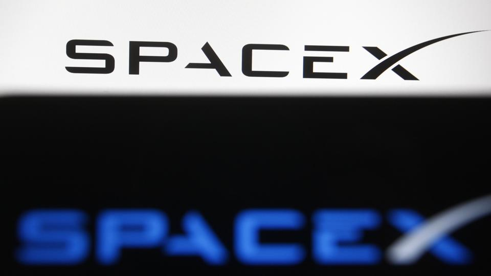 In this photo illustration a Spacex logo is seen on a...