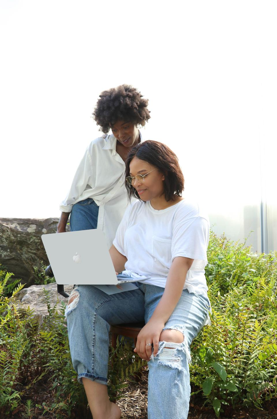 Two women looking at a laptop Earth and Olive