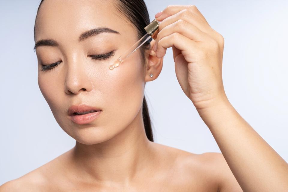 Asian beautiful female is applying eye serum