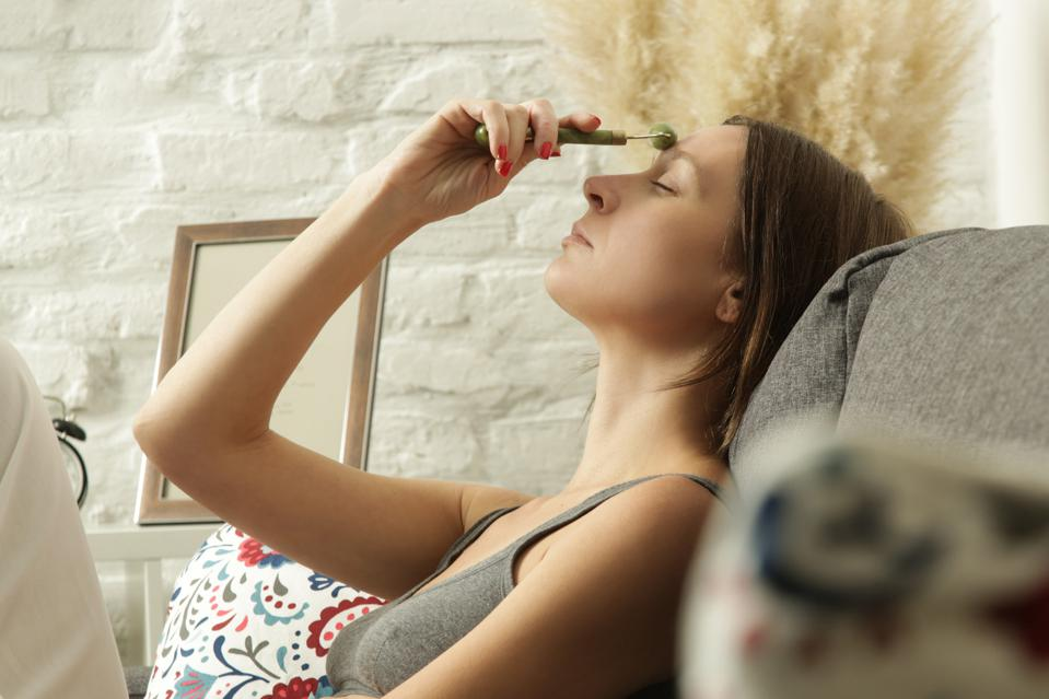 Face massage. Woman using jade face roller for skin care. Home spa concept.