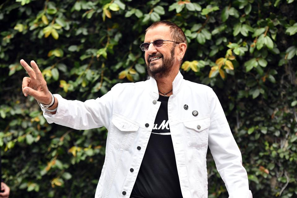 Ringo Starr peace sign in white jacket