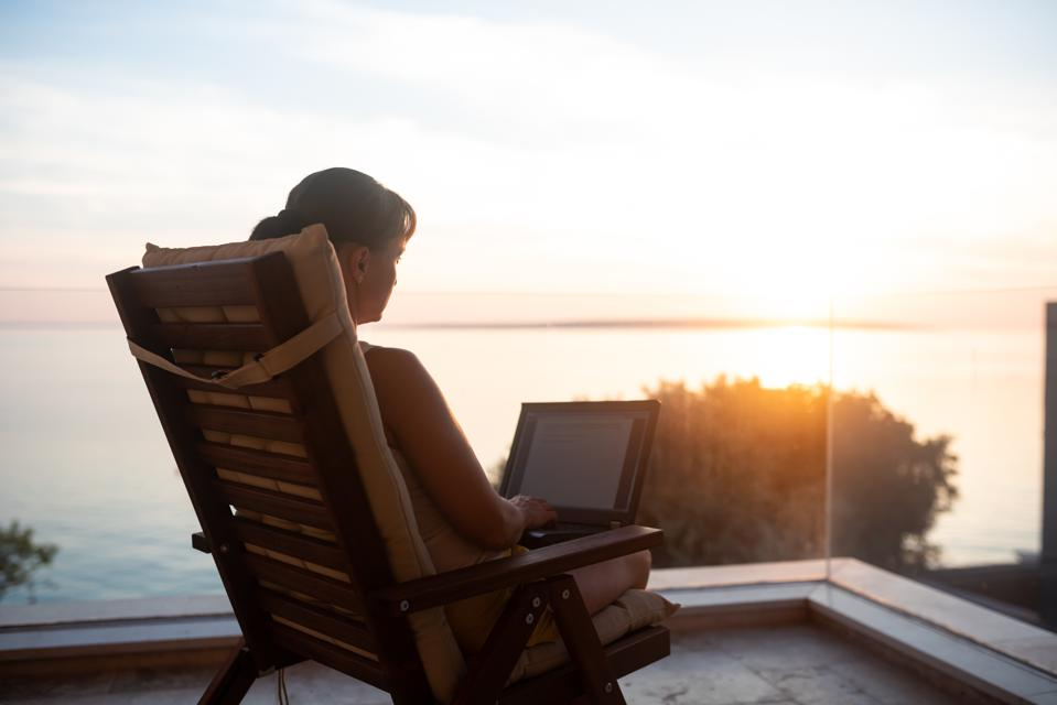 A digital nomad enjoying sunset and working remotely