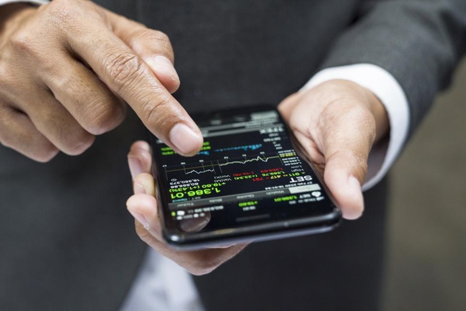 Businessman trading through mobile phone app