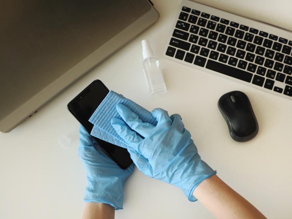 Disinfecting smartphone at workplace at home. Preventing disease by sanitazing devices