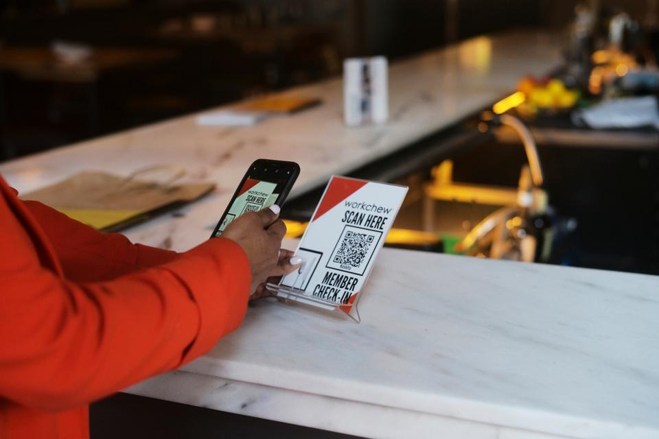 Image of person holding a sign and scanning a website link that allows WorkChew members to  check-in at the restaurant bar.
