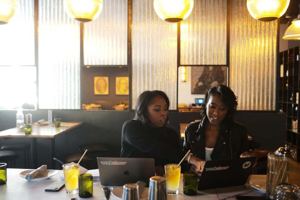 Co-founder Allyson McDougal (left) and Maisha Burt (right) on their laptops reviewing work.