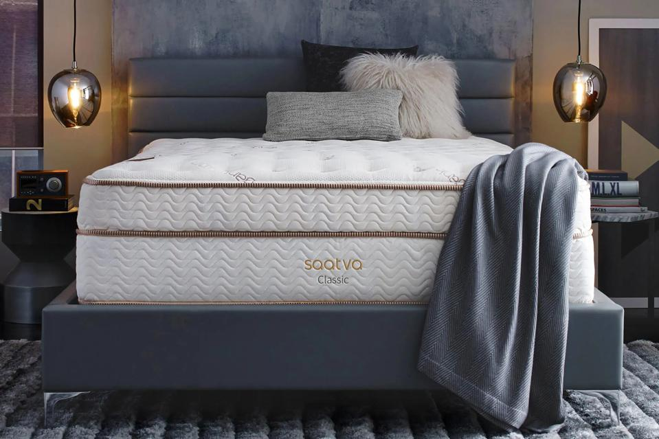 Saatva mattress set up in a bedroom with a gray throw on top.