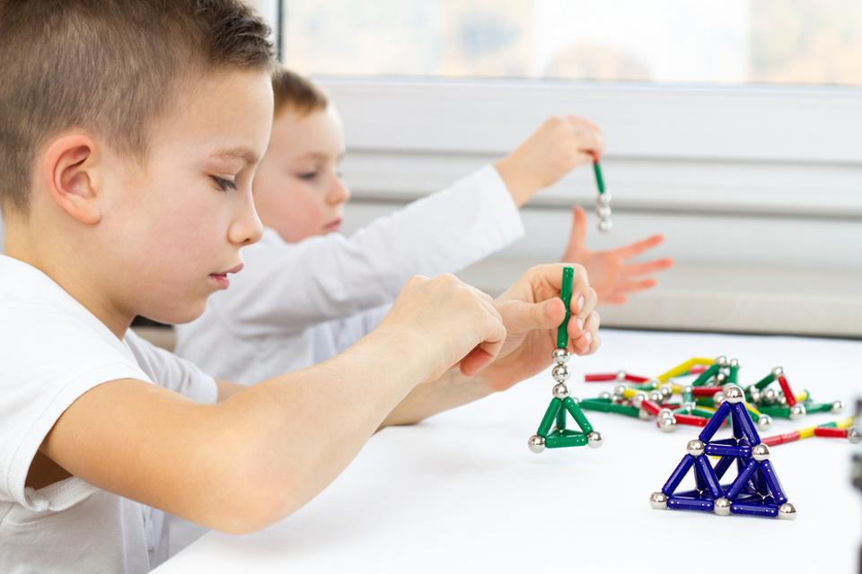 Close-up of kids playing board game while sitting at the table at home, magnetic sticks and balls for child development