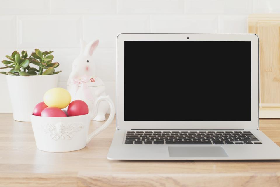 Happy Easter! Workspace with Laptop, Easter Eggs, Rabbit, Succulent On The Kitchen Counter, Close Up. Kitchenware In Modern Kitchen Interior. White Tiles Background