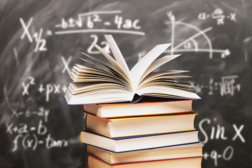 Stack of books in front of a blackboard
