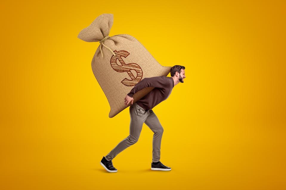 Vue latérale du jeune bel homme dans des vêtements décontractés portant un énorme sac lourd avec le symbole du dollar sur.