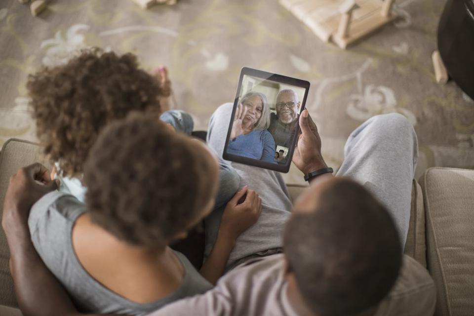 Family talking with grandparents on device.
