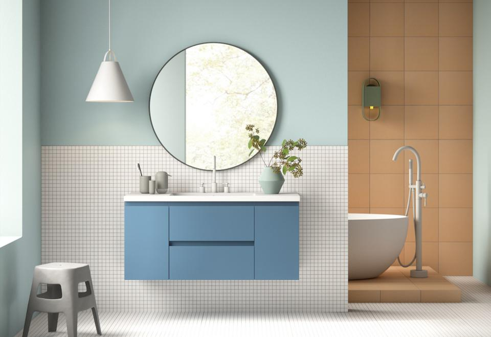 a bathroom with blue cabinetry and a round mirror