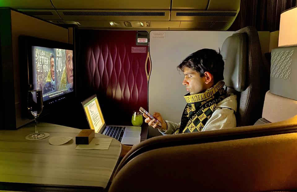 young man traveling on airline first class flying during coronavirus pandemic