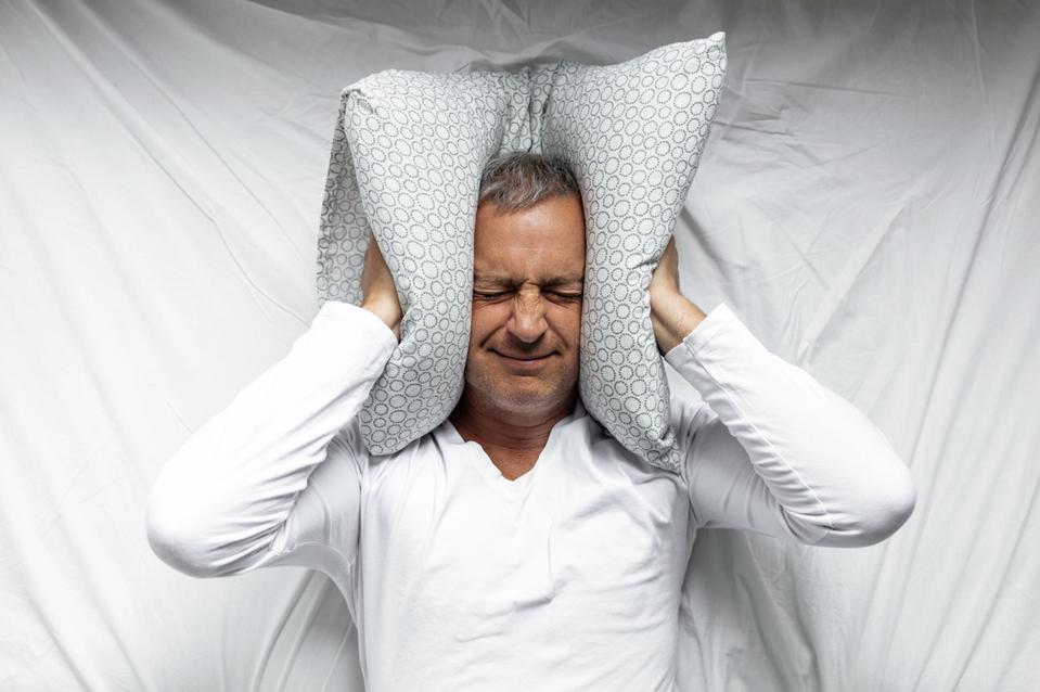 Man trying to sleep covering ears