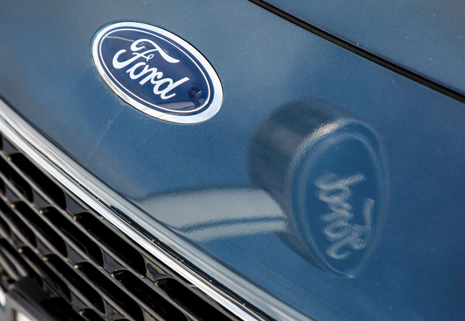 Ford logo on car and reflected in car hood.