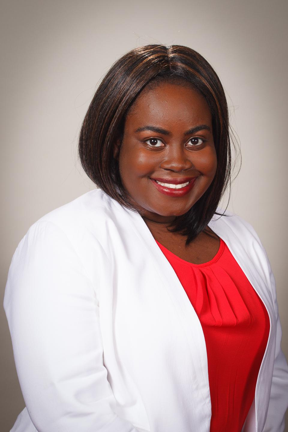 Jasmin Crentsil smiling in a white blazer and red shirt.