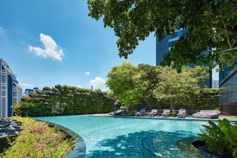 The pool at the Hyatt Regency Bangkok Sukhumvit hotel in Thailand is shaded by trees