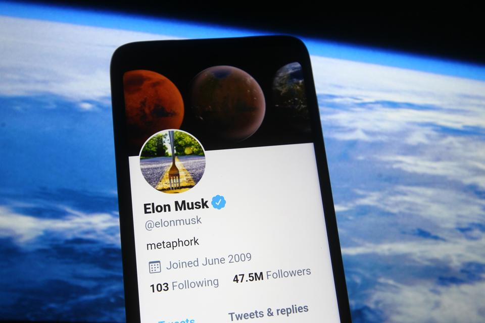 In this photo illustration a Twitter webpage of Elon Musk is...